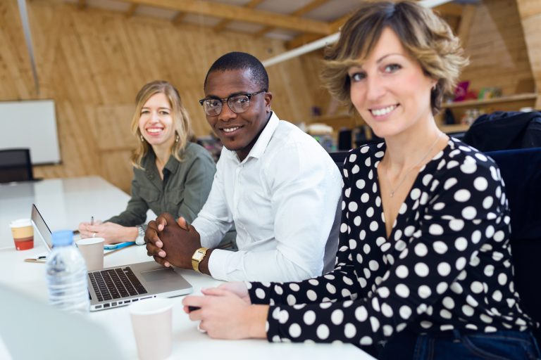 Successful smiling business team working together while looking